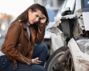 Young woman next to a wrecked car, our personal injury lawyer can help you with your car accident claim
