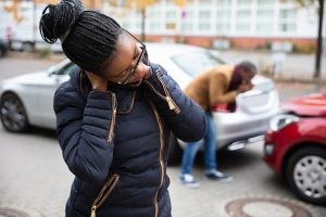 Woman holding neck from possible whiplash from car crash, our Gloucester injury attorneys can assist your with your claim.