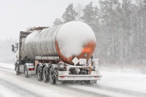 A semi-truck driving in the snow showing if you have been in an accident you should call Poquoson Truck Accident Lawyers