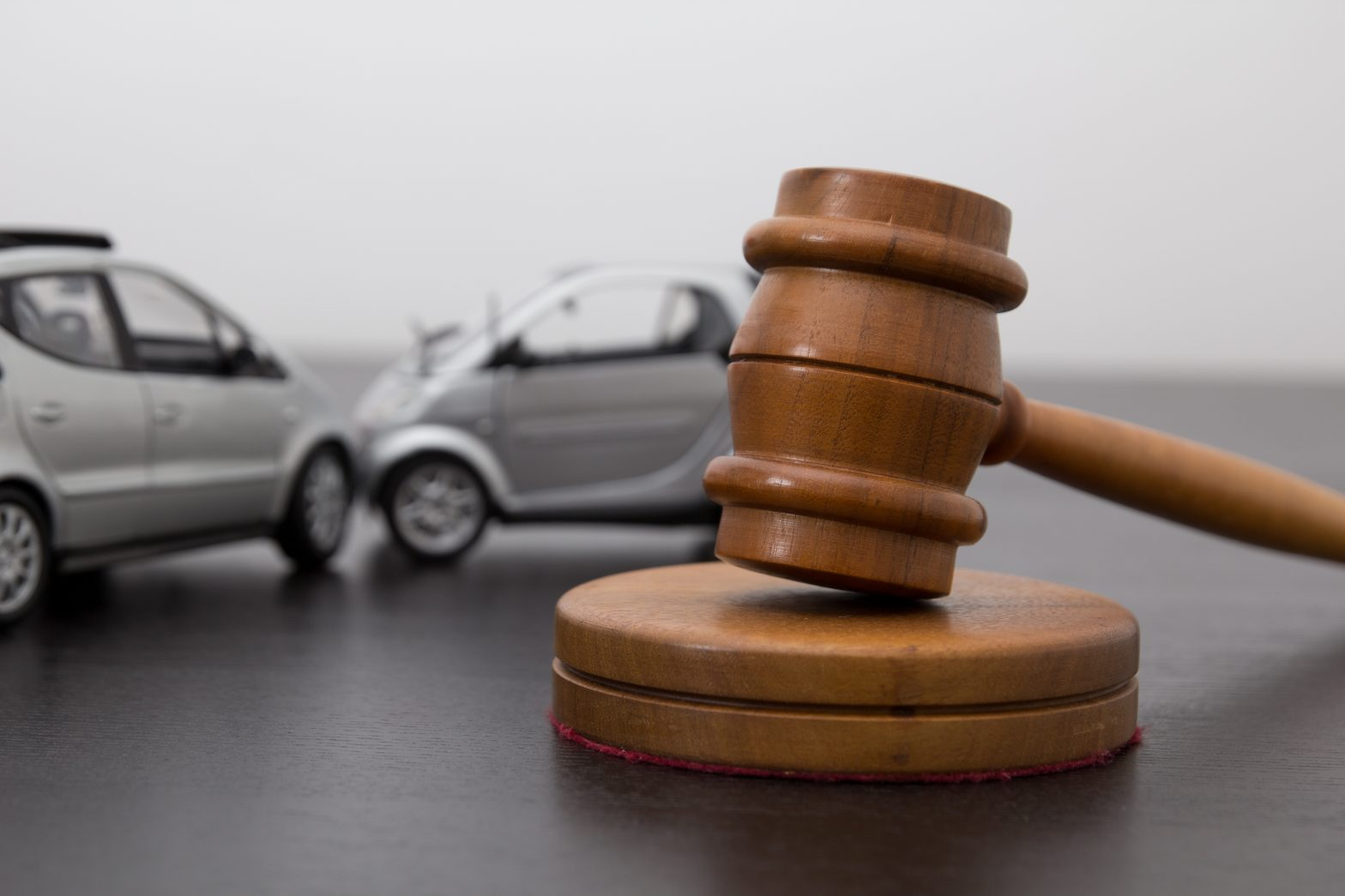 Two cars crashing and a gavel, meet with an Isle of Wight County Car Accident Lawyer to discuss your case.