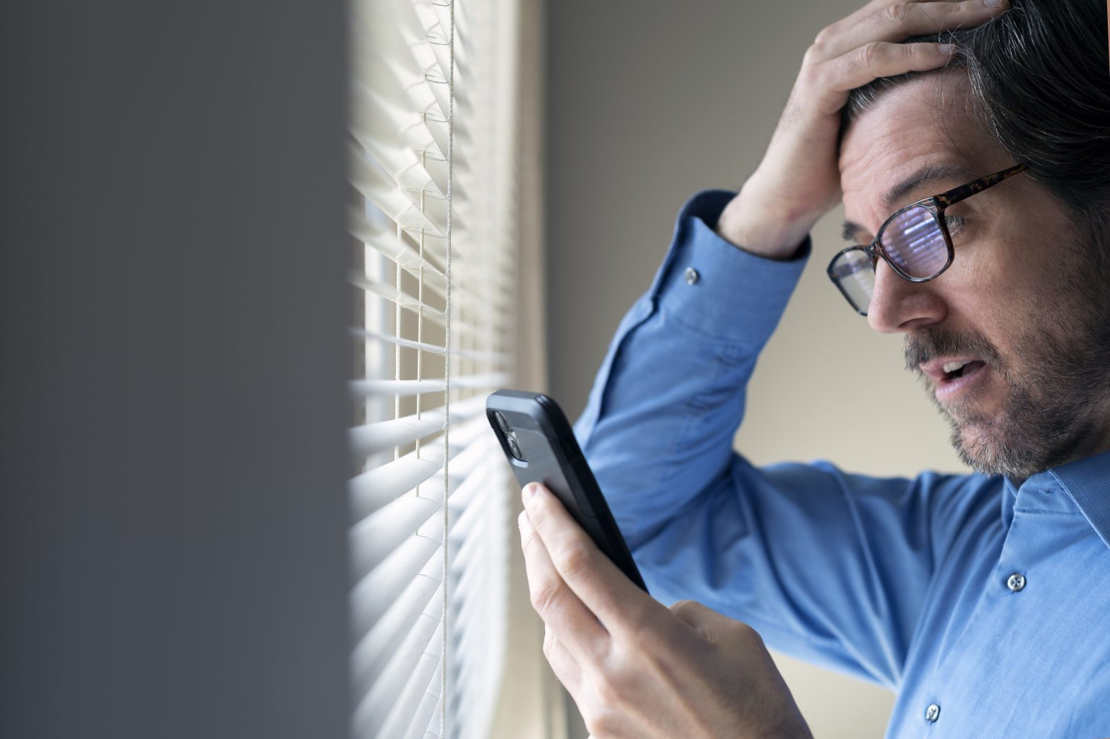 Man standing by window reacting to social media on his phone, when hurt in accident turn to Personal Injury Lawyer Virginia Beach.